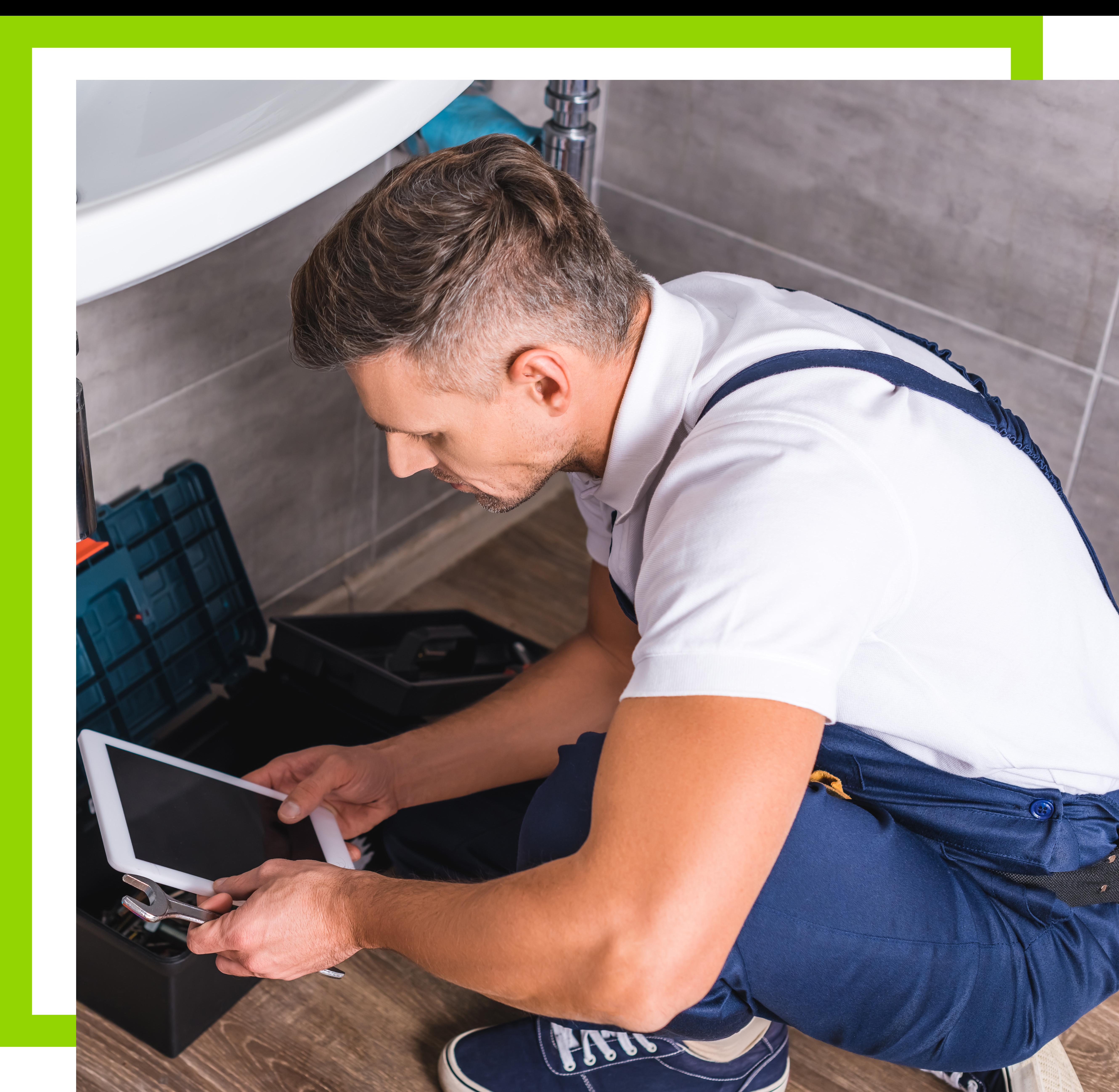 adult-repairman-sitting-on-floor-and-using-digital-X5RNBW7